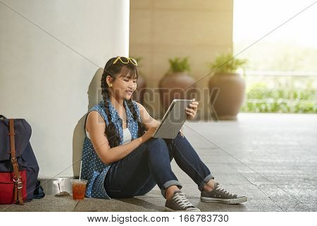 Asian female student using application on tablet computer