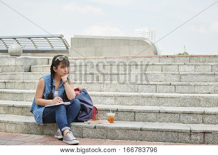 Pensive Vietnamese girl with textbook sitting on steps outdoors