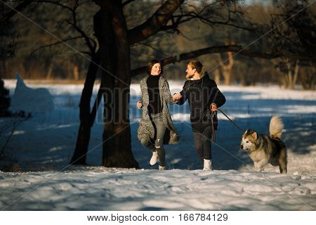 Girl and guy running in winter forest with dog malamute. They are running and holding hands.