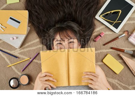 Cheerful Asian girl with a book lying on the floor, her belongings are around her