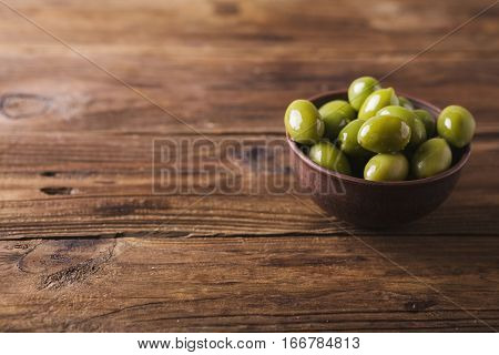 Green olives in a ceramic bowl on a wooden background. Background of olives. Background with green olives. Olives. Copyspace