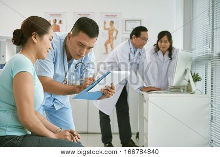 Male intern asking female patient for complaints