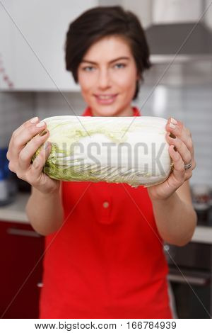 Smiling girl holding Chinese cabbage standing in kitchen