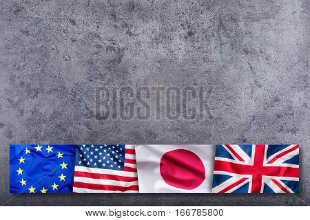 World flags concept.Collage of four countries world flags. European Union Great Britain American and Japan Flags on concrete background.
