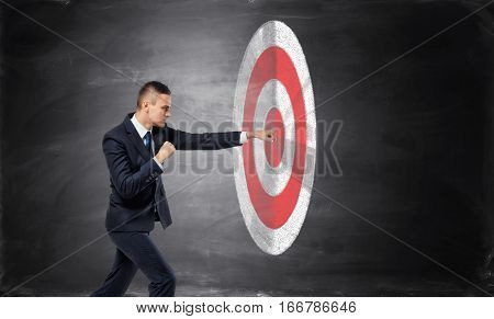Businessman is hitting with a fist a target on black background of concrete wall. Making money. Goals achievement. Business advancement