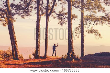 Vintage style Moment of loneliness. Young Man standing alone in forest outdoor with sunset nature on background Travel Lifestyle and survival concept
