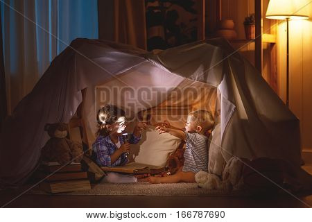 children boy and girl playing and frighten each other with flashlight in tent at night