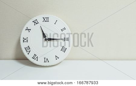 Closeup white clock for decorate show a quarter past eleven or 11:15 a.m. on white wood desk and cream wallpaper textured background with copy space