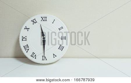 Closeup white clock for decorate show half past eleven or 11:30 a.m. on white wood desk and cream wallpaper textured background with copy space
