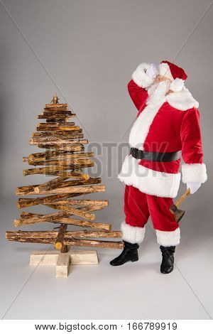 Tired Santa Claus making Christmas tree from firewood on grey