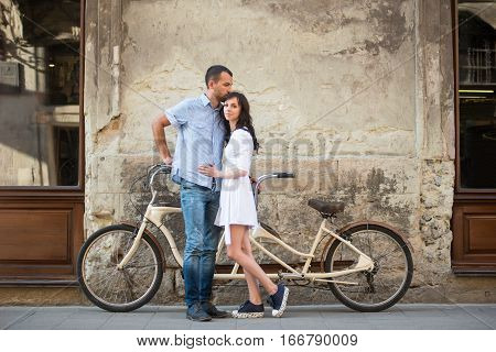 Young Couple With Retro Tandem Bicycle At The Street City