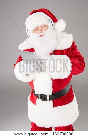 Happy Santa Claus listening music with headphones and using digital tablet