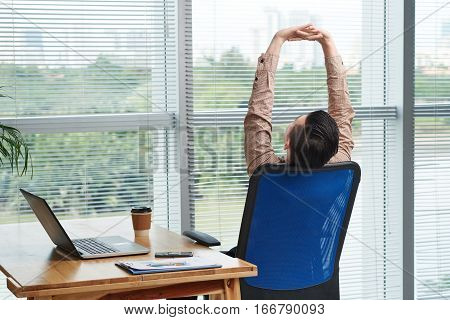 Rear view of businessman stretching on his chair