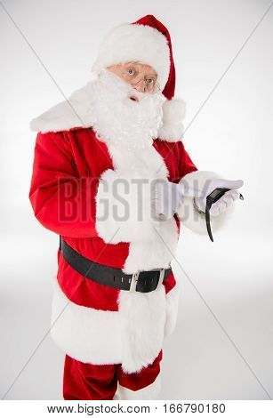 Happy Santa Claus pointing on smartwatch and looking at camera