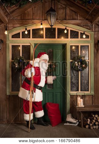 Santa Claus standing with skis and knocking in door