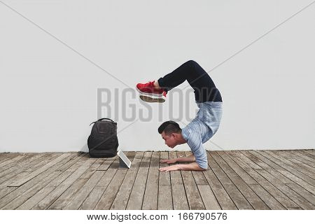 Asian young man performing handstand according to video on tablet computer