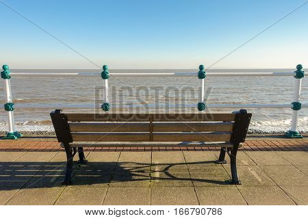 Empty wooden bench on a promenade overlooking the sea on a sunny day in winter.