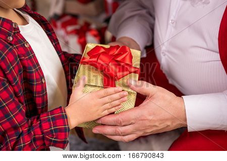 Cropped image of Santa Claus giving present to child