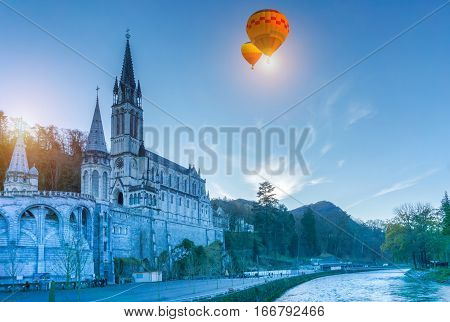 Colorful hot air balloons flying over Rosary Basilica in the evening Lourdes Hautes-Pyrenees France