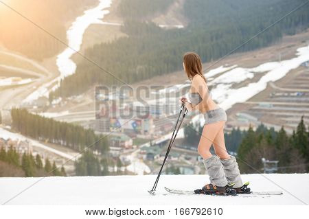 Naked Woman Skier Standing On The Snowy Slope Of The Mountain, Wearing Ski Equipment