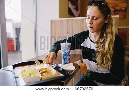 young woman eating fastfood in a cafe