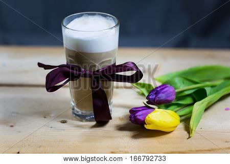 Latte macchiato with tulips, on wooden background