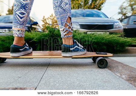 close up of female legs in colorful pants standing on longboard. Longboard girl on the street