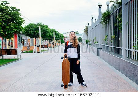 Longboard girl on the street. smiling young woman with a longboard and standing on the street.