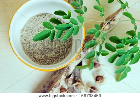 Moringa Leaf And Seeds On Wooden Board Background