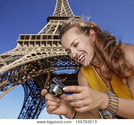 Happy Young Woman Viewing Photos In Front Of Eiffel Tower