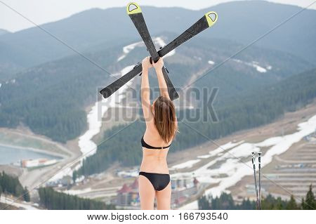 Back View Of Unrecognizable Female Skier Is Standing On The Slope And Holding Skis Above Head