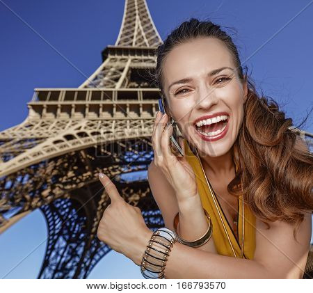 Woman Speaking On Cell Phone And Pointing Against Eiffel Tower