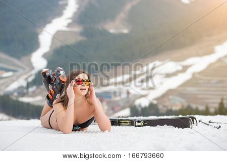 Portait Of Beautiful Female Skier Is Lying On The Snowy Slope In The Mountains