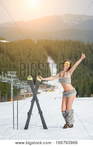 Portrait Of Beautiful Naked Female Skier With Skis. Smiling Woman Is Showing Thumbs Up On Snowy Slop