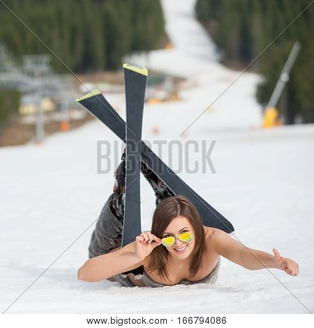 Young Sexy Naked Skier Is Lying On Snowy Slope Near Ski Lift At Ski Resort