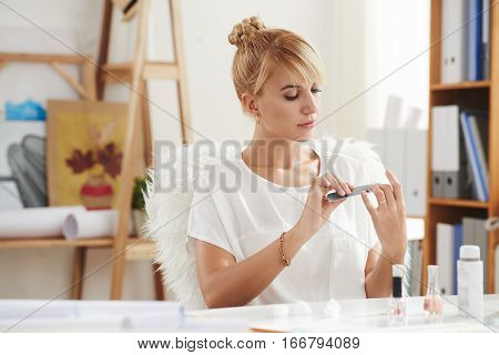 Pretty young woman filing her nails at workplace