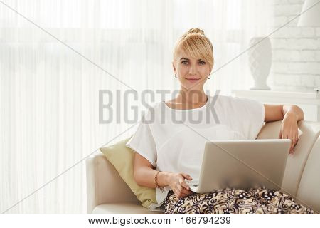 Portrait of beautiful woman sitting on comfy sofa with laptop