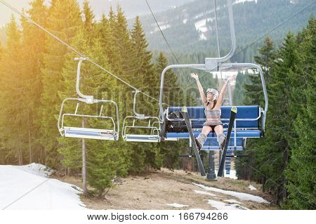 Young Happy Sexy Skier Is Rising Hand Up On Ski Lift And Riding Up To The Top Of The Mountain With S