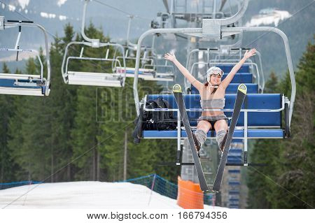 Happy Girl Skier Is Sitting On Ski Lift, Rising Hands Up And Riding Up To The Top Of The Mountain
