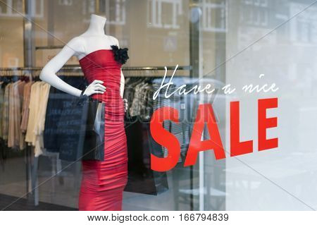 fashion doll with dress for women and the word sale on display window of clothing store