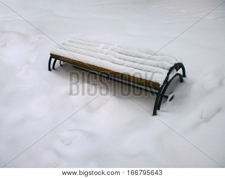 City bench covered with snow in the city of Krivoy Rog in the Ukraine in the winter