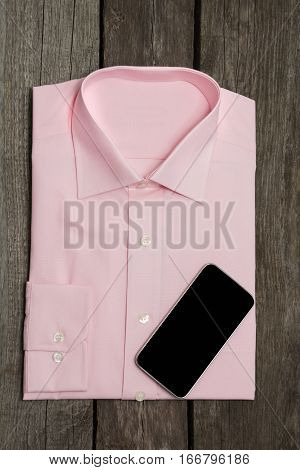 New pink shirt and mobile on wooden background