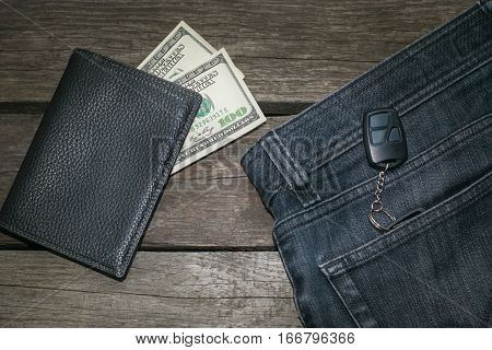 Black wallet american dolla and key from car in jeans on wooden board.