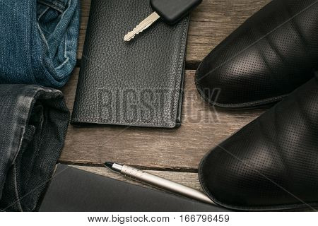 Male set for day from wallet jeans and car key on wooden board.