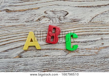 ABC spelling from the plastic letters on wood background for design