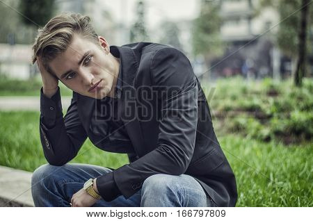 Close up Disappointed Young White Man Sitting at Street Side with Grassy Landscape at the Background