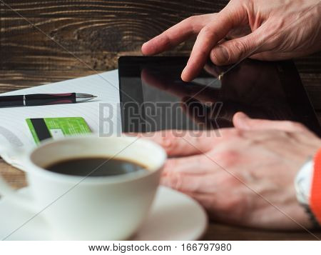 Man shopping online using laptop, drinking coffe. close-up side view.