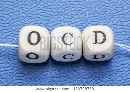 Word Ocd (obsessive Compulsive Disorder) On A Wooden Cubes On A Blue Background