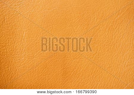 Texture of genuine leather close-up, red-based orange. With place for your text, for background use.