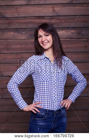 Mid shot portrait of positive girl posing with hands on hip looking sideways. Wearing checked white and blue shirt with jeans. Model posing against wooden background